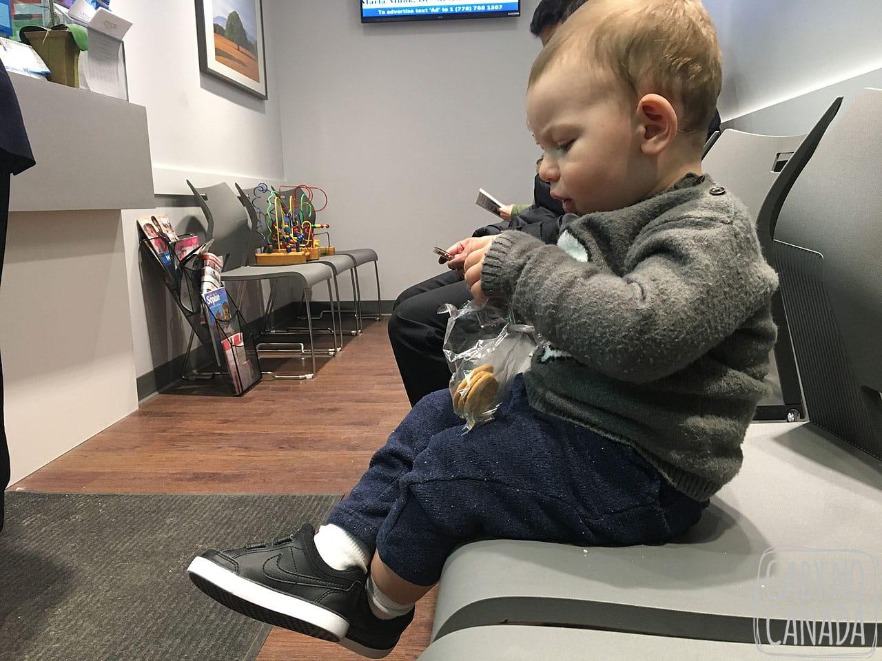 Thomas lendo um livrinho enquanto espera para ser atendido em uma clínica.